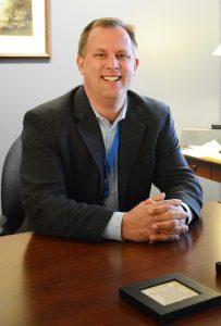 Ray VanderLaan sitting at a desk smiling