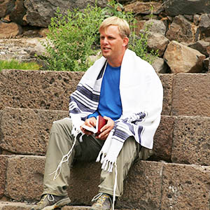 Todd Lanting sitting on stone steps in Israel wearing a traditional Tallit prayer shawl.