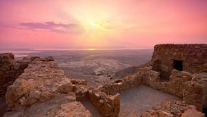 Sunset over Israel seen from an ancient structure perched on a mountainside.